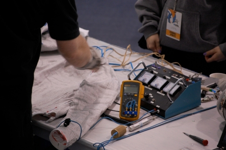 Officials check the electronic wiring that registers touches on fencers' suits. Scoring bouts can be pretty complicated: Different parts of the body are fair game depending on the weapon, and officials can overrule the electronics — which, did I mention, don't always work?