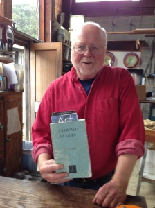 Glass blower Jim Kingwell poses with with a book---by a Penn Stater-that he says he couldn't create his art without.