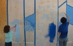 Painting the construction wall outside the Stuckeman Family building.